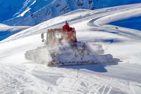 snow grooming machine: Heavy snow grooming machine preparing ski slopes in the Alps