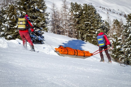 downhill skiing: Two members of a ski patrol helping an injured skier down the mountain