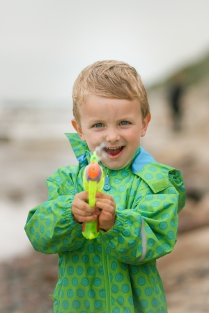 Young boy splashing out water with his water gun  photo
