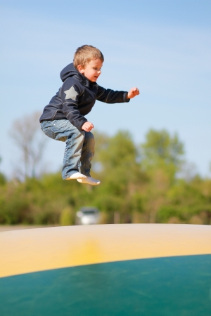 baby 4 5 years: Young boy jumping on green and yellow trampoline