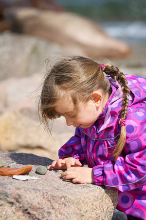 A young girl with long hair examining her collection of pebble Stock Photo - 24575835