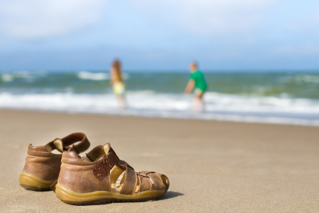Close-up of worn brown kids sandals on sandy beach. Blurred background with two kids playing at the waters edge. Ideal as illustration for summercasualleisure purposes.