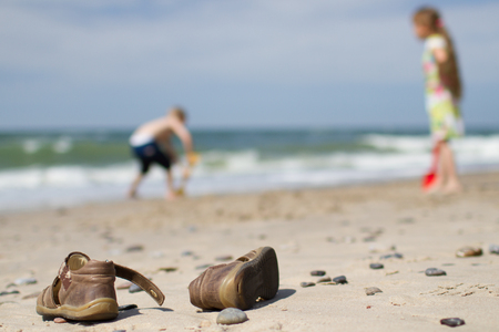 northern european: A pair of brown leather sandals placed casually on a somewhat rocky Northern European beach. Blurred background with a boy and a girl digging in the sand. Stock Photo