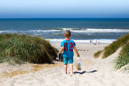 Young boy overlooking horizon over water and walking through eroded sand dunes on his way to a beach in Northern Europe during summer time. Boy is wearing t-shirt and swim trunks and carrying his plastic toys for water play. photo