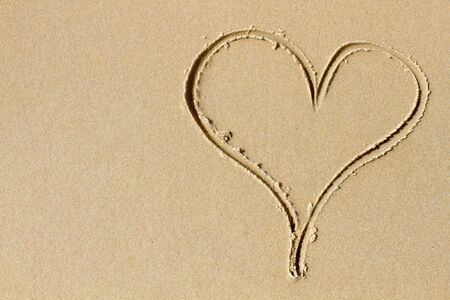 valentine s day beach: Casual drawing of a sand heart  Shot from directly above  Plenty of copy space
