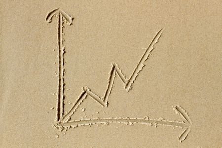 business trending: Upwards trending line chart drawn in the wet sand of a sunlit beach  Ideal as illustration of concepts related to growth, success and  professionel business services
