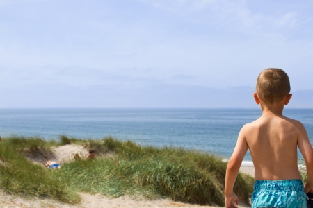 horizon over water: Young boy is having a panoramic view of the entire horizon over water at the North Sea shore in Western Jutland, Denmark  Plenty of copy space