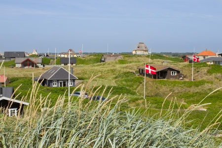 Danish holiday houses scattered among the sand dunes at the North Sea coastline in Soendervig, Denmark  Picture taken on a sunny summer day  Danish flags are visible on the picture