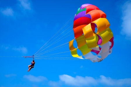 towed: A parachute being towed at sea with a clear blue sky in the background.