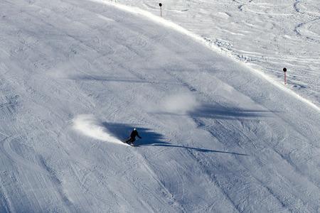 Skier heading down ski run marked with black sign.