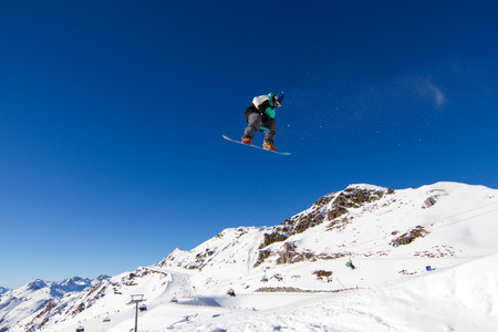 Snowboarder performing a big air in snow park. photo