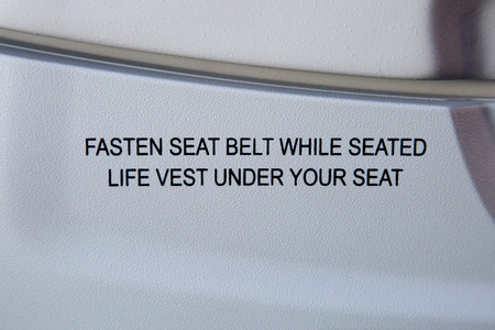 Fasten seat belt notice on back of aircraft chair  photo