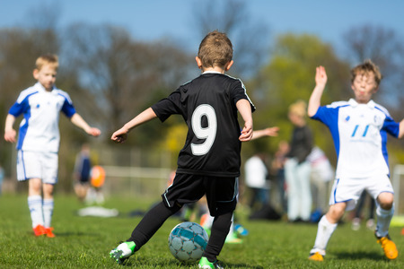 Boys playing soccer outside during summer time  Trademarks have been removed  Stock Photo
