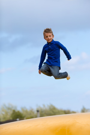 looking towards camera: Boy jumping up and down on bouncy pad.