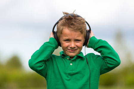 looking towards camera: Boy listening to music with luxury headphones. Trademarks have been removed.