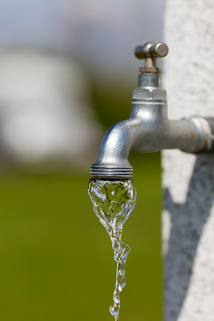 Water flowing from outdoors water tap on a sunny day. Stock Photo
