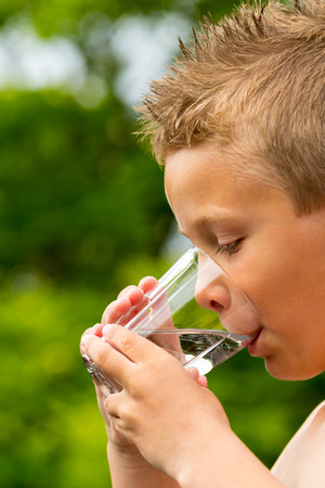 Young caucasian boy drinking from glass with fresh water outdoors during summer time. photo