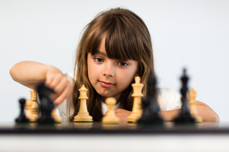 Young caucasian girl with long hair playing a game of chess. photo