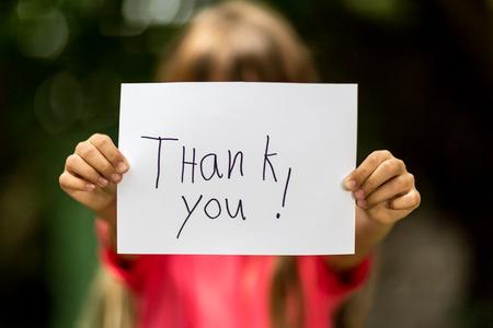 hand sign: Wazig meisje met een stuk papier met de woorden: Dank U voor haar.
