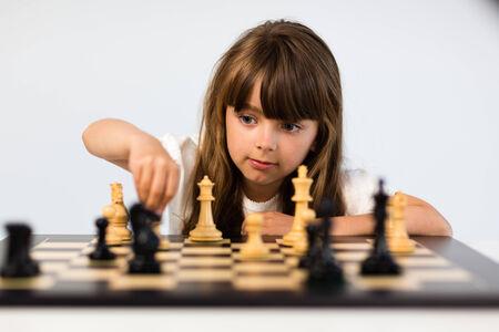 jugando ajedrez: Muchacha caucásica joven con el pelo largo que juega una partida de ajedrez. Foto de archivo