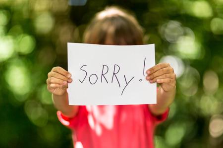 désolé: Fille flou tenant un morceau de papier avec le mot Désolé devant elle.