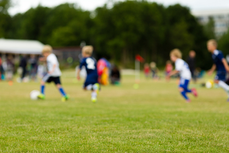 Blur shot of young boys outdoors soccer match in summer time. photo
