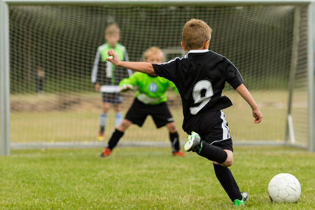 Goalkeeper and penalty kicker in the midst of a penalty kick during a youth soccer match. Focus is on the kicker.