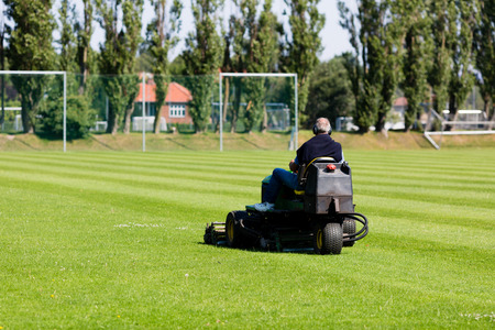 Greenkeeper mowing a perfect green lawn used for soccer  photo