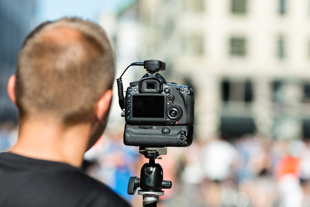 tripod mounted: Male photographer preparing for photography assignment on a crowded street. Stock Photo
