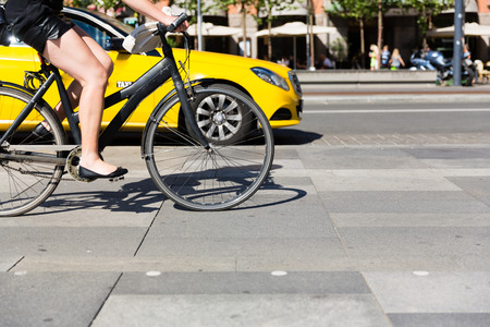 bicycle wheel: Unidentifiable female person riding a bicycle in the city centre. Stock Photo