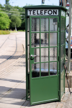 phone booth: Classical old green phone booth with open door.