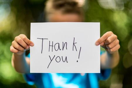 merci: Gar�on floue tenant un morceau de papier avec les mots Merci en face d'elle. Banque d'images