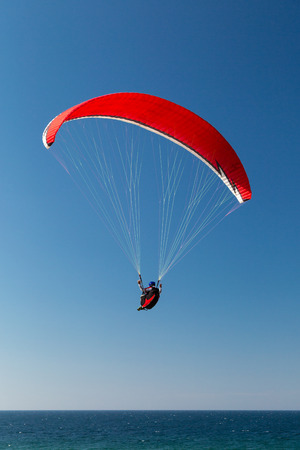 hovering: Single paraglider hovering in the sky on a sunny day. Stock Photo