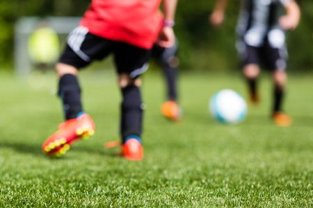 boy ball: Picture of kids soccer training match with shallow depth of field. Focus on foreground.