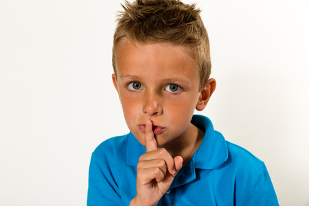 zipped: Caucasian boy doing a Please Keep Quiet gesture towards the camera. Studio shot with white background.