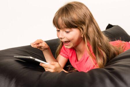beanbag: Girl lying on black beanbag with her tablet. Studio shot on white background. Stock Photo