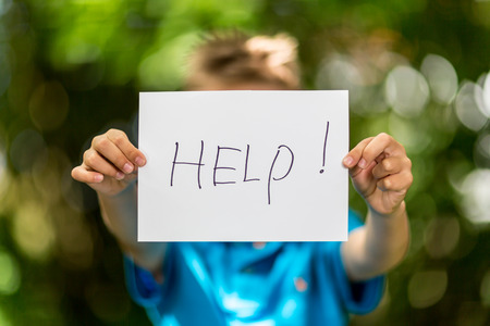 Blurred boy holding a piece of paper with the word Help in front of her. Stock Photo
