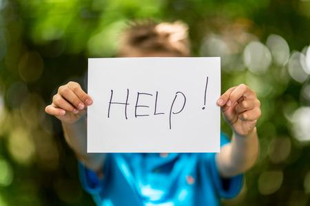 Homályos fiú kezében egy darab papírt a szót Help előtte.