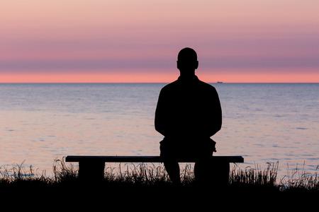 personen: Silhouet van mannelijke persoon tegen een kleurrijke horizon. Stockfoto