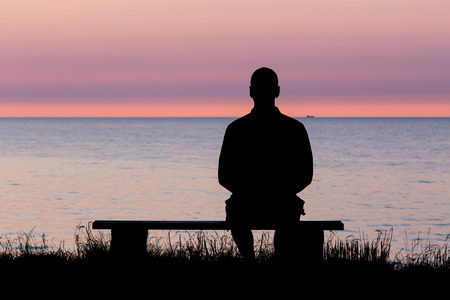 sitting in the bench: Silhouette of male person against a colorful horizon. Stock Photo