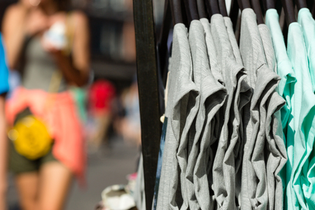 Grey and turquoise blouses on hangers outside a store. photo