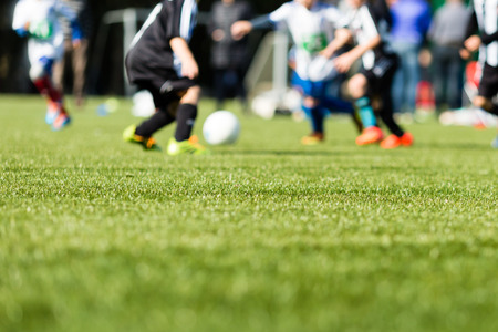 action blur: Picture of kids soccer training match with shallow depth of field. Focus on foreground.