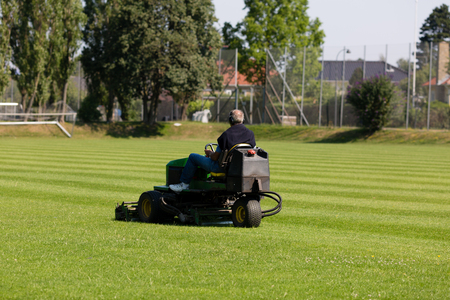 Greenkeeper mowing a perfect green lawn used for soccer.