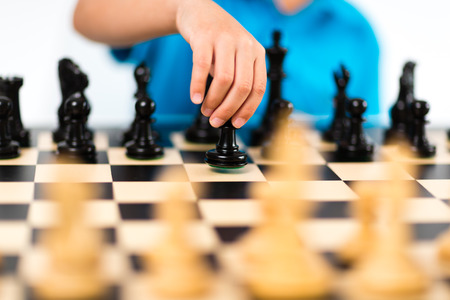 Young caucasian boy playing chess on white background.