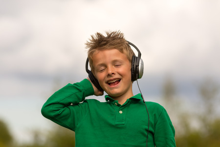 highend: Boy holding his large headphones while singing along. Trademarks have been removed.