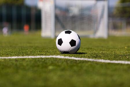 ballon foot: Ballon de football noir et blanc sur un terrain de soccer vert.