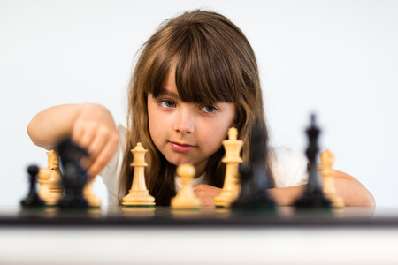 Young caucasian girl with long hair playing a game of chess.