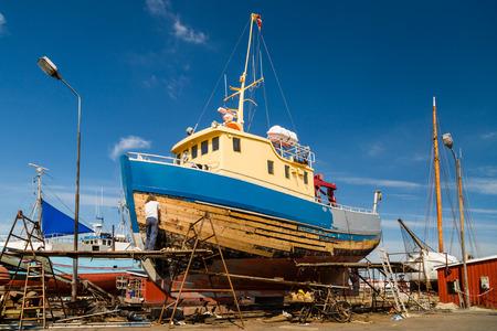 refurbishing: Medium-sized boat undergoing maintenance and repairs while in dock.