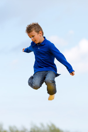 Boy hanging in mid-air.  Trademarks have been removed. photo