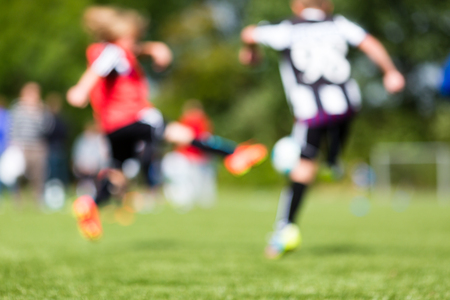 Abstract blur of kids soccer training match during summer time. photo